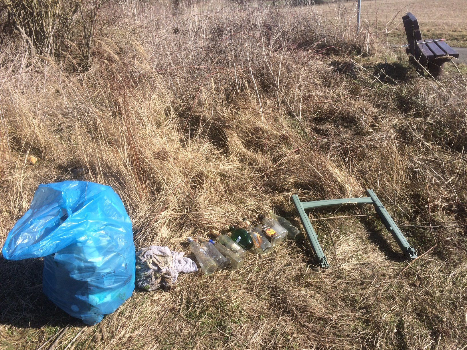 Müll gesammelt rund um eine Bank für Spaziergänger - kein Abfalleimer in der Nähe!
